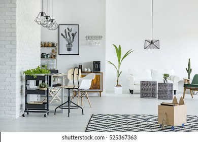 White apartment with pattern carpet, brick wall, table and sofa
