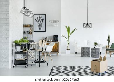 Appartement blanc avec moquette motif, mur en brique, table et canapé