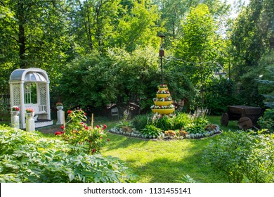 White arbor in antique style in a green garden with beds, trees and flowers. Sokol metro station area, Moscow.