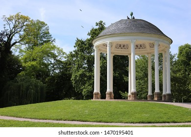 White arbor with columns in a green park. Arbor with white columns on the lawn