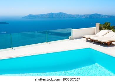 White architecture on Santorini island, Greece. Luxury swimming pool with sea view. Famous travel destination