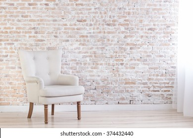 White Armchair On Brick Wall Background Near Window