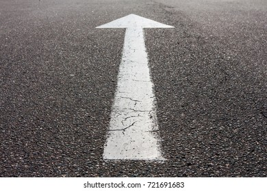 White arrow direction on gray asphalt with copy space