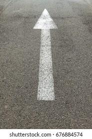 White arrow on ashpalt road.