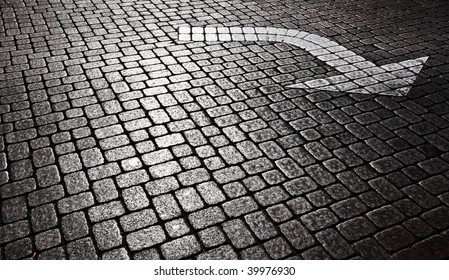 white arrow on cobblestone