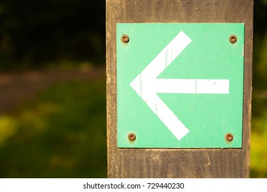 White arrow on green background turn left sign on wooden post with greenery foliage bokeh