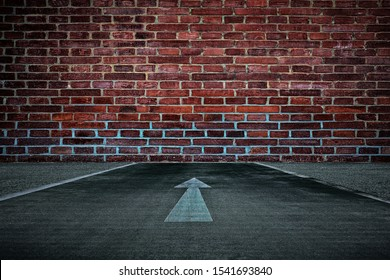 White Arrow on the Road Straight to the Old Brick Wall Background, Suitable for Business Dead End Concept.