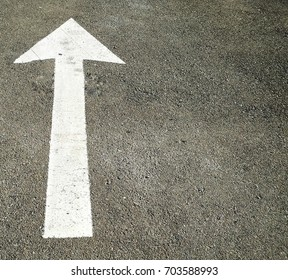 The white arrow on the road surface with go straight signal
