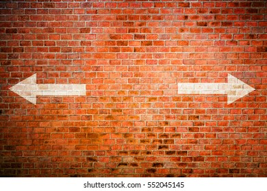 White arrow on vintage brick wall, decision making concept