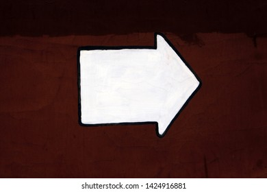 White arrow painted on dark red concrete wall