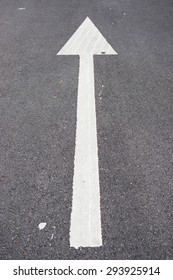 white arrow point on the road, sign