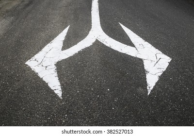 White arrow sign  on asphalt