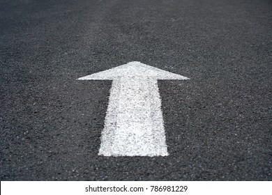 White arrow sign on asphalt road, Traffic symbol on street, Surface rough Texture Background.