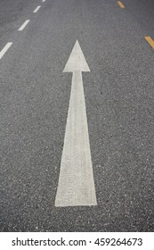 White arrow sign on paved road.