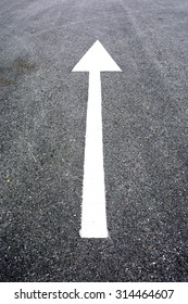 white arrow sign on the road