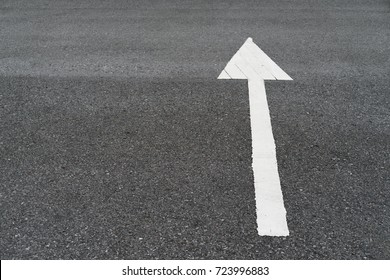 White arrow sign on street along the road texture background with copy space
