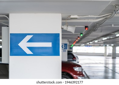 white arrow Signage on the indoor carparking pole, tell driver which way to go and location in parking lot.