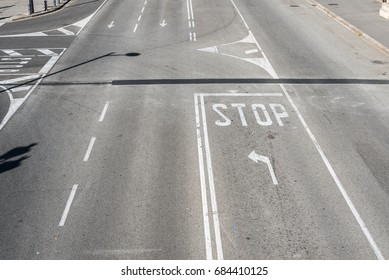White arrows and stop symbol on the asphalt