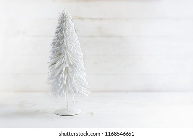 white artificial christmas tree from flocked wire on a rustic white wooden background with copy space, selected focus