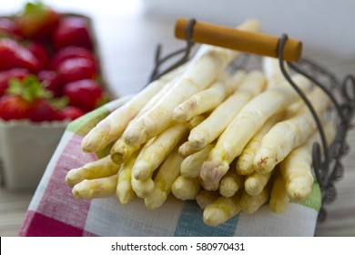 White asparagus in a basket with fresh strawberries