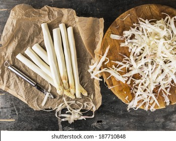 white asparagus with peelings on brown crumpled paper with knife