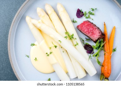 white asparagus and sauce hollandaise as closeup on a plate with sliced fillet steak