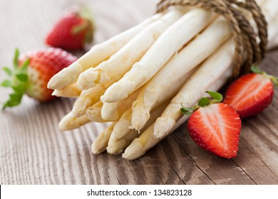 white asparagus and strawberries on wooden table