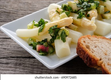 White asparagus tips salad with herbs and rubarb and slice of bread