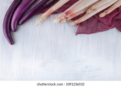 white aspargus and purple violet aubergines decorated with napkin on a kitchen table, can be used as background