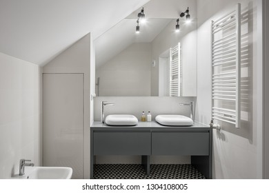 White, attic bathroom with two basins and big mirror