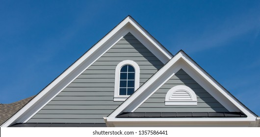 White attic half round gable vent louver ,cathedral window,  on horizontal lap vinyl siding on a new construction luxury American single family home in the East Coast USA with blue sky background