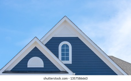 White attic window vent on blue siding, gable, corbel, louver on a new construction luxury American single family home in the East Coast USA with blue sky background