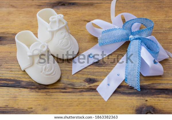 White Baby Boots with Blue Ribbon Bow on Rustic Wooden Surface, Gender Reveal Concept