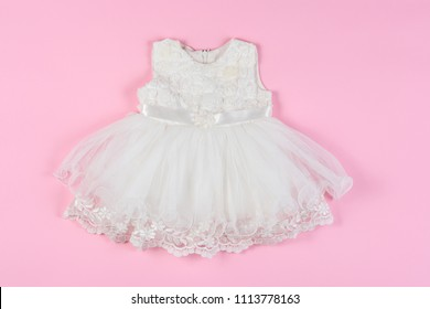 White baby dress with flowers on a pink background. Concept of children's clothing, fashionable children's clothes.