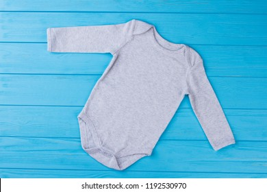 White baby onesie pajama. Top view. Blue wood background.
