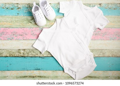 White baby onesie and sneakers over pastel wooden background. Good for insert your design. Mock up