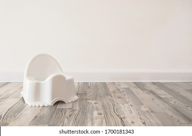 white baby potty on the floor. white pot on a white background. pot on the wooden floor. pot on a white wall background. children's pot in a bright interior. learn to go to the toilet. large space