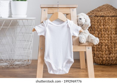 White baby short sleeve bodysuit mockup for presentation cute sublimation designs. Minimalistic photos of romper for toddlers in scandinavian interior with minimalistic decoration