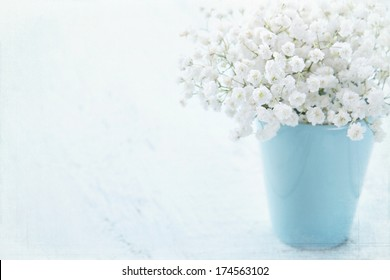 White baby's breath flowers in a vase on light blue textured vintage background