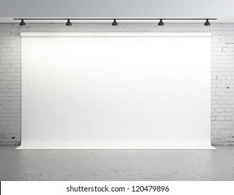 White backdrop in room with brick wall