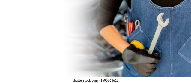 White background. Asian man auto mechanic using a wrench and screwdriver to working service car in garage.