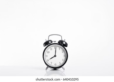 White background with black alarm clock on table