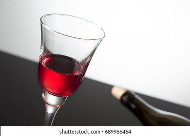 white background black floor glass wine and wine bottle