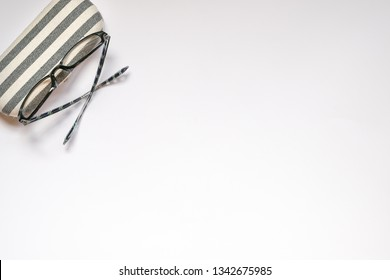 White background with copy space and reading glasses and its casing on the side