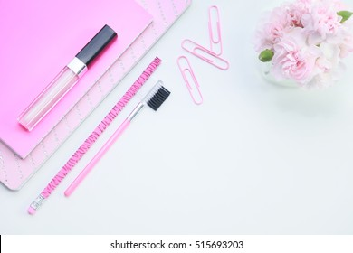 A white background desktop mock up of a feminine pink notebook, lipstick, pencil, paper clips and fresh miniature carnation flowers.