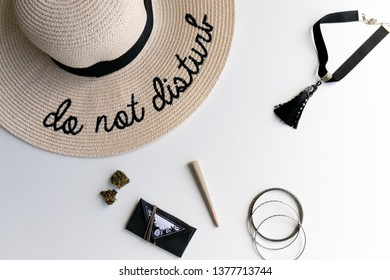 White background with a Do Not Disturb hat, a marijuana joint, buds and a weed pouch for festivals