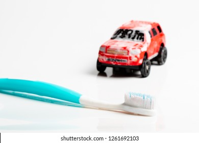 a white background in the foreground lies a toothbrush, in the back of the car is red