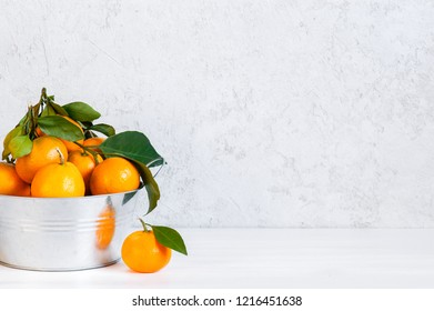 White background with fresh ripe tangerines in the metal bowl, copy space