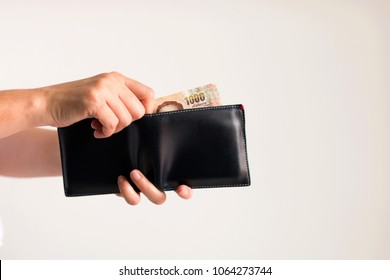 White background photo of hands holding a wallet and another hand bring Thai money from it to pay for something.