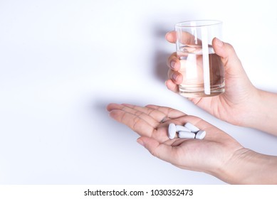 White background tof two hand holding a glass of water and medicine pills.